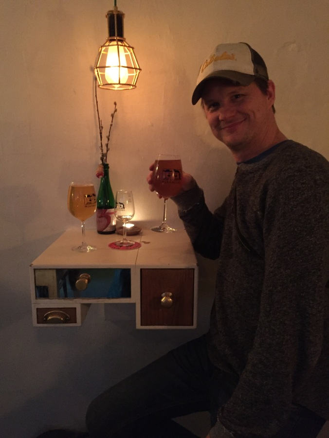 man sits at small bar table attached to wall