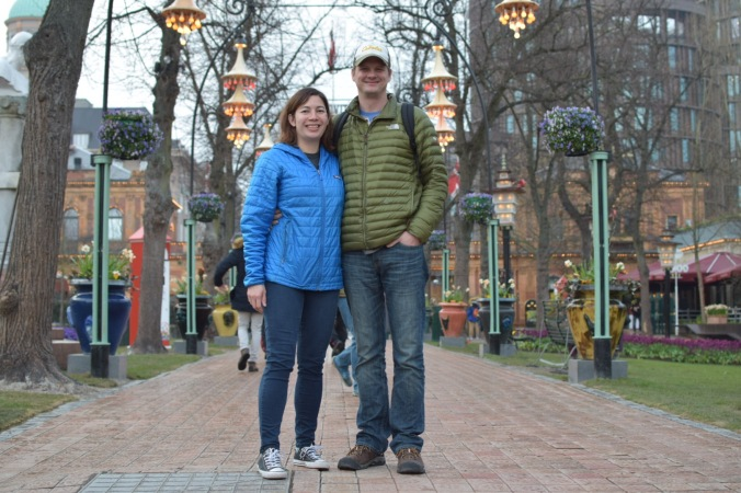 couple stands on walkway under colorful lanterns