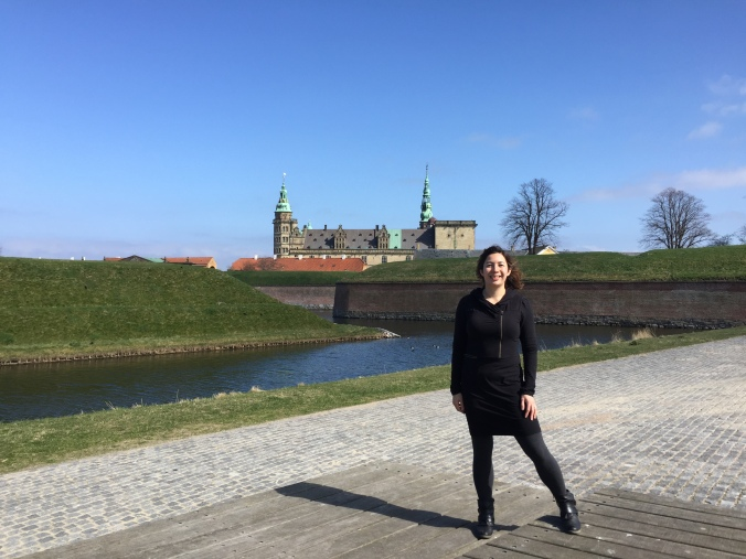 a woman stands in front of a Danish castle