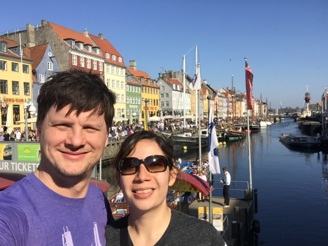couple standing in front of the row houses in Nyhavn