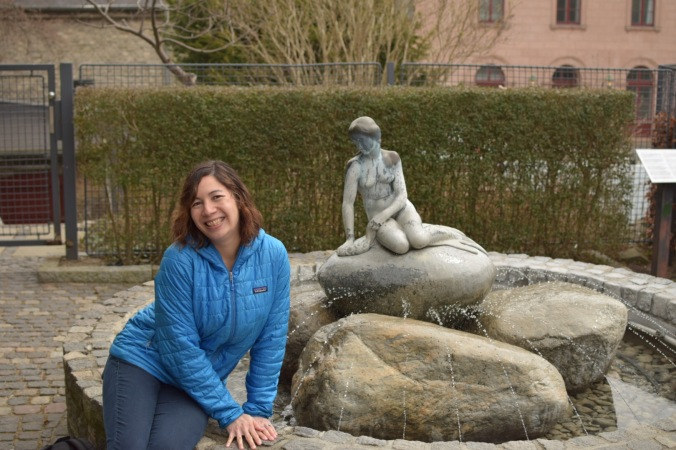 woman next to Little Mermaid statue