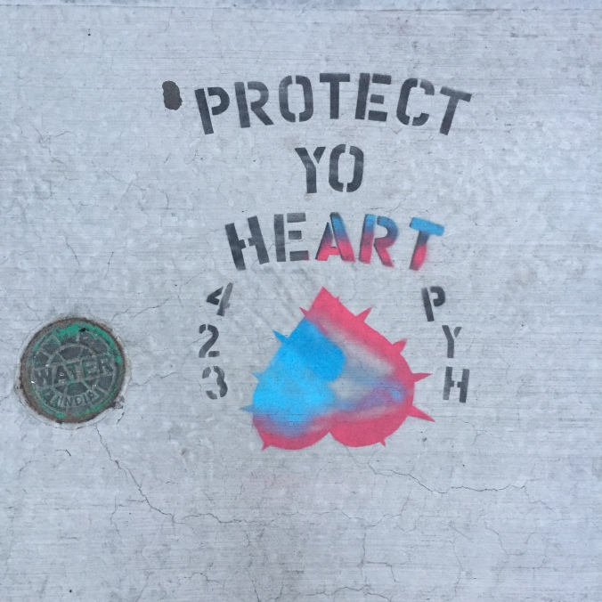 "sidewalk graffiti that says ""Protect Yo Heart"""