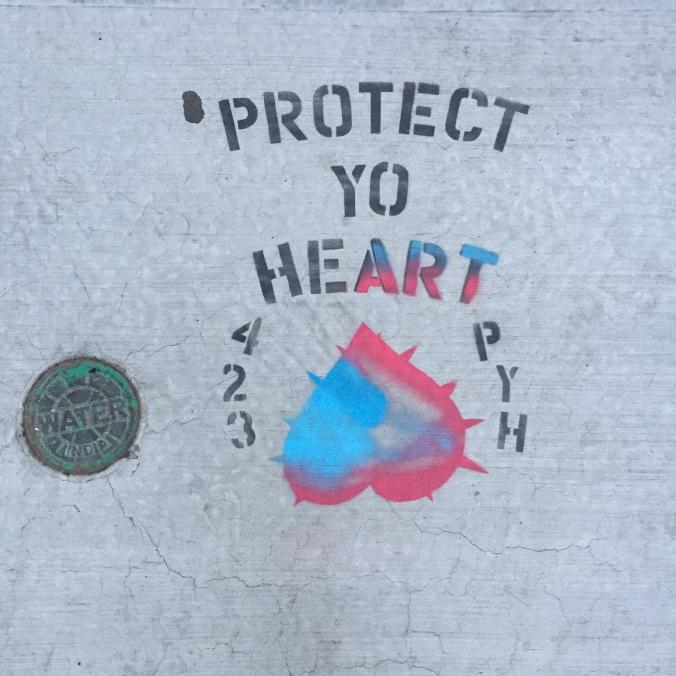 "sidewalk graffiti that says ""Protect Yo Heart"""