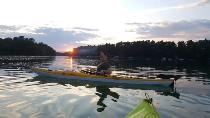 woman kayak on a lake during sunset