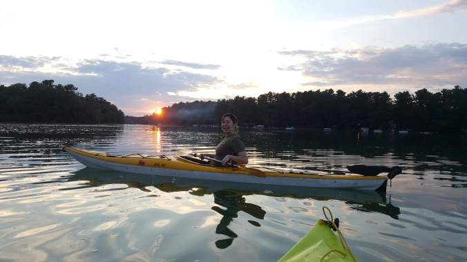 woman kayak on a lake during sunset