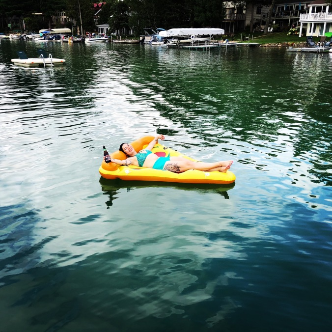 woman floating on pizza-shaped floatie on a lake