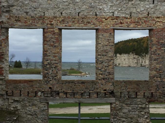 partial brick wall of an abandoned building, with three open windows facing Big Bay De Noc