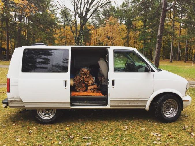 a white chevy astrovan with its sliding door open to reveal a large stack of firewood inside