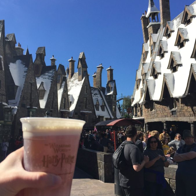 a cup of butterbeer in front of the rooftops of Hogsmeade