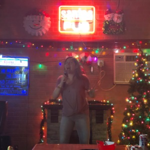 a woman sings karaoke in a karaoke bar inside a double-wide trailer.