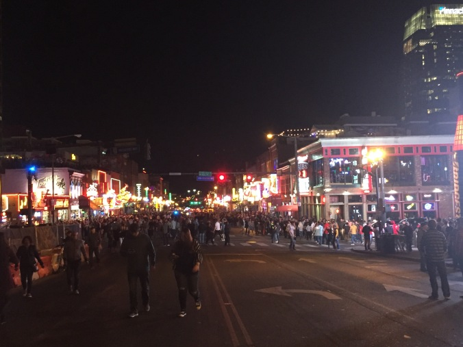 Broadway at night, a street filled with neon signs and sidewalks full of pedestrians