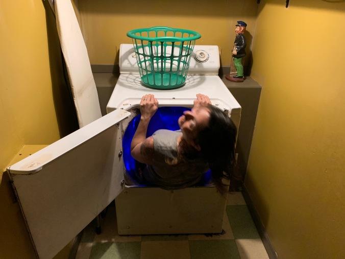 A woman crawls into a blue tunnel inside a washing machine.