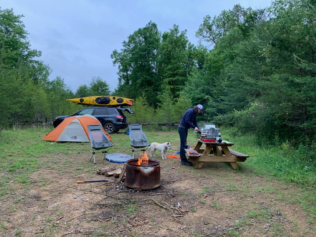 A camping scene: In the foreground, there is a campfire with two folding chairs set up nearby. In the background, a gray and orange domed tent is set up in front of a Subaru with a kayak strapped to the roof rack. On the right, a man stands over a picnic table cooking on a portable stovetop.